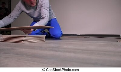 Professional workers laying wooden oak laminate boards on...