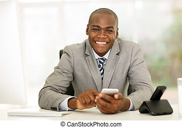 young african businessman using smart phone in office