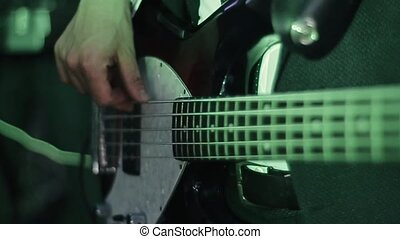 Professional young bass player playing guitar solo. The musician performs at a concert and has a good command of the instrument. Close up view of hands . Lighting colors change.