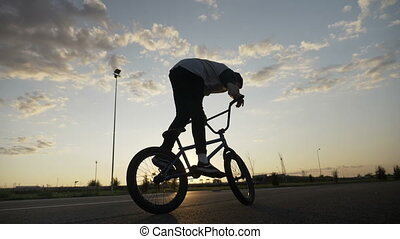 Professional young bicycler jumping on his bike rotating the...