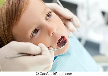 Professional young dentist is treating his small patient