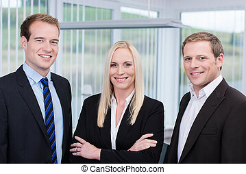 Professional confident young happy team made of two handsome men and a blond long haired woman bethween them, all smiling and wearing business clothes, in the office