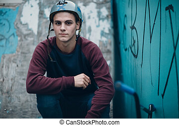 Professional young sportsman cyclist portrait with bmx bike and helmet at skatepark