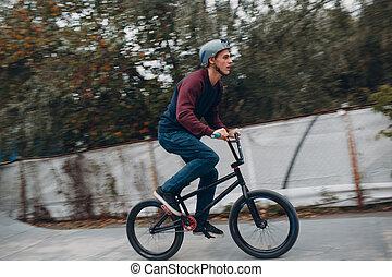 Professional young sportsman cyclist with bmx bike at skatepark. Motion blur.