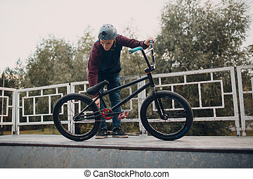 Professional young sportsman cyclist with bmx bike at skatepark.