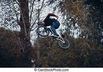 Professional young sportsman cyclist with bmx bike doing trick at skatepark