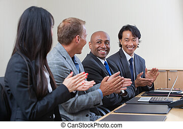Professionals applauding during a business meeting -...