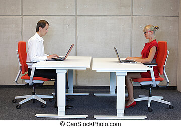 professionals at work stations - business man and woman...