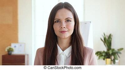 professionnel, appareil photo, bureau, sourire, jeune, confiant, femme affaires, regarder