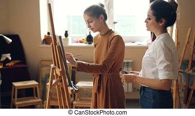 professionnel, prof, de, art, école, est, fonctionnement, à, appliqué, étudiant fille, peinture, image, et, conversation, partage, expérience, intérieur, dans, salle travail, entiers, de, artworks.