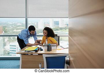 professionnels, rire, dans, bureau, vidéo regardant, images, sur, smartphone