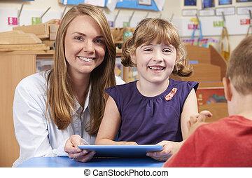 professor, ajudando, elementar, scool, pupila, para, uso, tablete digital