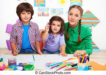 professor, com, crianças, desenho, e, olhando câmera