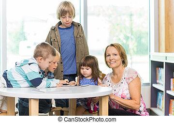 professor, com, estudantes, usando, tabuleta, computador, em, biblioteca