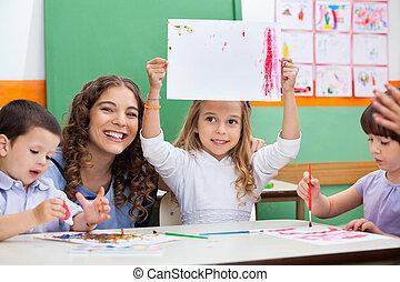 professor, com, menina, mostrando, desenho, escrivaninha