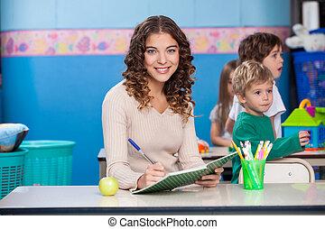 professor, escrevendo livro, com, jogar crianças, em, fundo