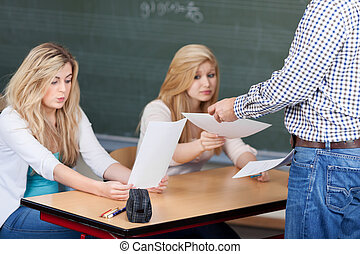 Professor Giving Exam Papers To Nervous Students At Desk