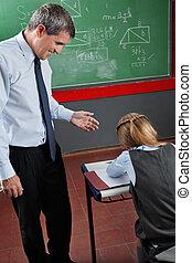 Professor Looking At Schoolgirl In Classroom