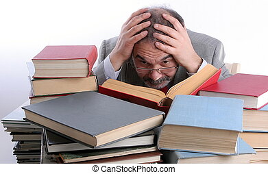 Single male is reading a book. Sitting behind a pile of books. Holding head in hands