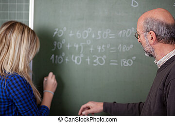 Professor Teaching Student At Classroom Desk