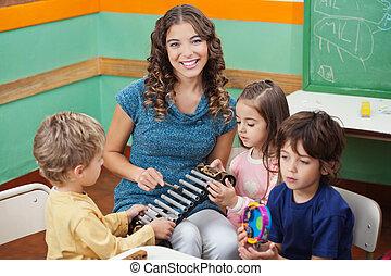 professor, tocando, xilofone, com, estudantes, em, pré-escolar