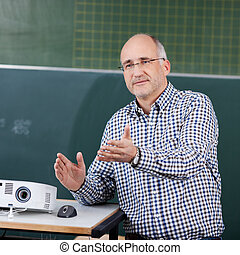 Professor With Projector And Mouse Gesturing In Classroom -...