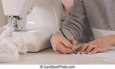 Proffesional seamstress making pettern with pencil