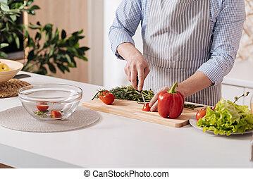 Proficient cook preparing healthy dinner in the kitchen
