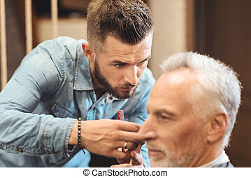 Proficient hairdresser designing haircut in the barbershop