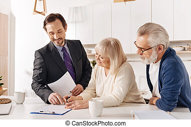 Proficient real estate agent meeting with elderly couple of clients