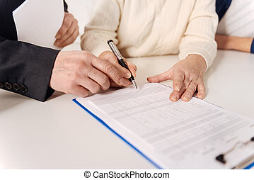 Proficient social security advisor signing document with elderly couple
