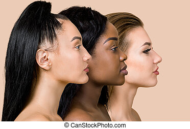 Profile close up portrait of three beautiful multiracial women, Asian, African and Caucasian, with different types of skin and hair, posing over beige background. Natural beauty of women. Copy Space