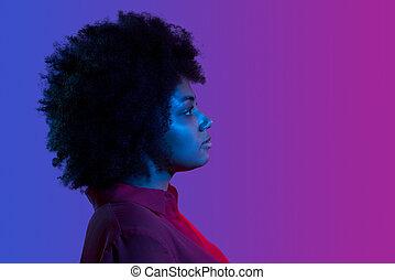 Profile closeup portrait of african woman looking forward, neon light studio portrait