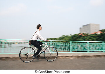 Profile image of an active businessman riding a bicycle on the way to job