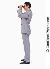 Profile of a businessman using binoculars