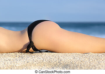 Profile of a butt of a woman with a bikini sunbathing resting on the beach