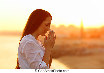 Profile of a concentrated woman praying with hands together at sunset