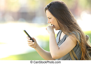 Profile of a girl angry with mobile phone - Side view of a...