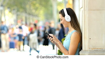 Profile of a girl listening to music from a phone in the street