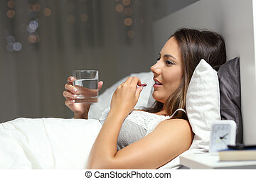 Profile of a girl taking a pill on a bed in the night at home