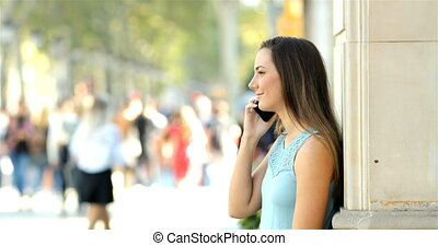 Profile of a girl talking on phone in the street
