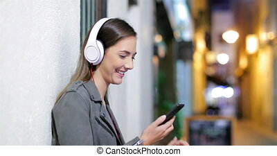 Profile of a happy girl listening to music in the night