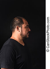 profile of a latin american man on black