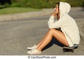 Profile of a pensive teenager girl sitting on a skate in the street