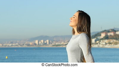 Profile of a woman breathing smiling on the beach