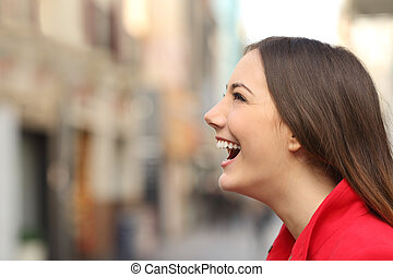 Profile of a woman face laughing happy in the street