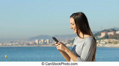 Profile of a woman texting on phone on the beach