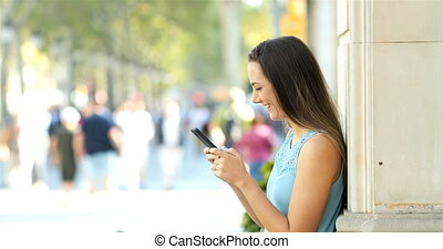 Profile of a woman using a phone in the street