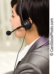 Profile of an Attractive Young Mixed Race Woman Smiles Wearing Headset In An Office Setting.