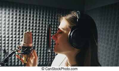 Profile of beautiful girl singing in sound studio. Young female singer emotionally recording new song. Woman sings to microphone. Working of creative musician. Show business concept. Slow motion